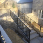 black metal railings on staircase leading to house garage