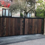 Large dark wooden gate with black metal railing finish in front of large white brick house