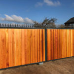 Large wooden gate with black metal railing finish