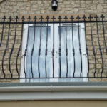 curved black metal railings sat atop flat roof in front of balcony doors