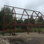 metal steel building framework in front of tree line