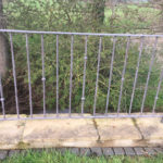 Unpainted metal railing installed on stone wall overlooking small river
