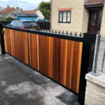 black metal and wooden finish gate at front of large house