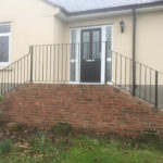 metal railing installed on small stairs leading up to house front door