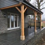 black iron railings installed in front of slate patio porch area of house